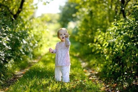 Little baby in a forest holding a leaf