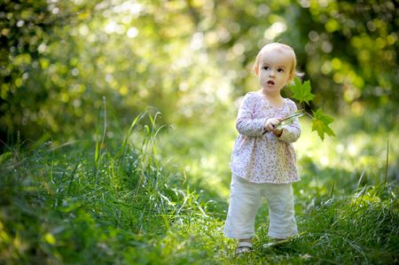 Little nice baby in a forest holding maples leaves