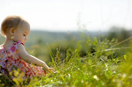 Little baby girl sitting on the edge of a cliff Stock Photo