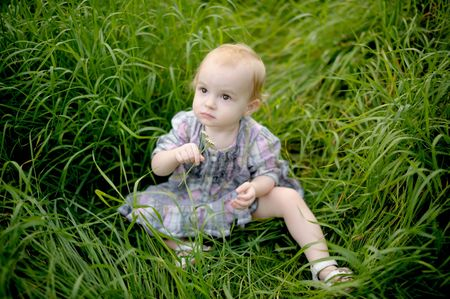 Little baby is sitting in a meadow in the grass holding flower Stock Photo - 5667944