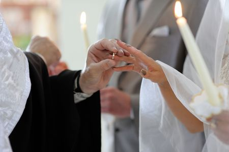 Priest is putting the ring on brides finger during orthodox wedding ceremony photo