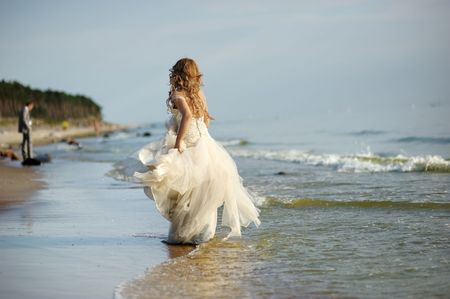 Bride walking along sea coast in the wedding dress photo