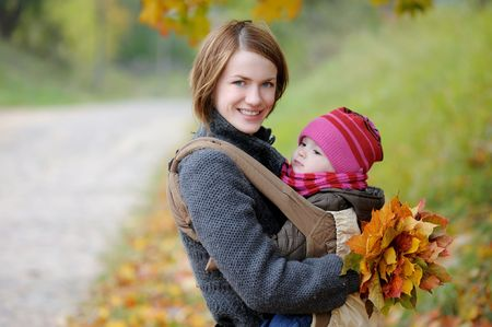 Young mother with her little baby in a carrier Stock Photo - 5794558