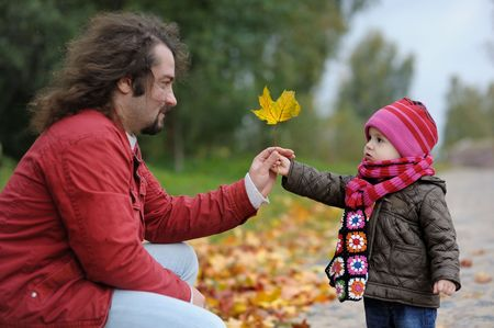 Young father and his little baby girl in an autumn park photo