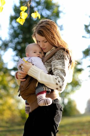 Young mother with her little baby in a carrier Stock Photo