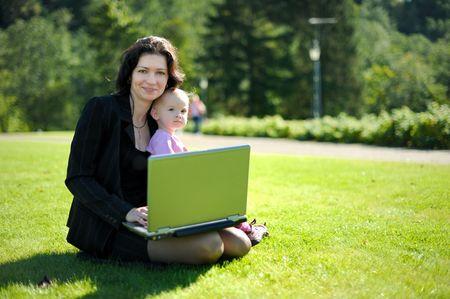 work together: Mooie jonge dame met een baby en een laptop in een park