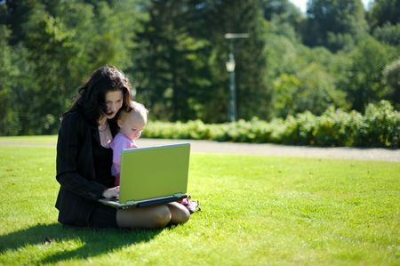 Beautiful young lady with a baby and a notebook in a park photo