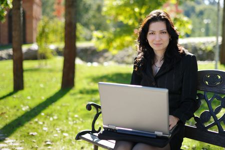 Beautiful young lady with a notebook in a park photo