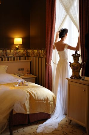 Bride and groom are standing agains the window looking outside Stock Photo - 6227067