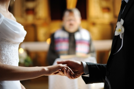 Bride and groom are holding each others hands during church wedding ceremony