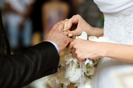 Bride is putting the ring on grooms finger