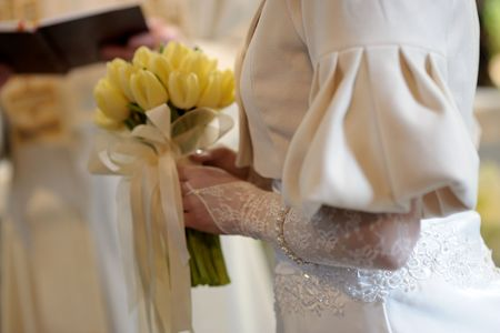 Brides close-up with yellow tulip durign church wedding ceremony photo