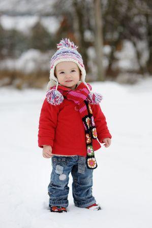 Little winter baby girl in red coat