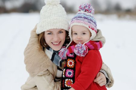 Little winter baby girl and her young mother in a park Stock Photo - 6226368