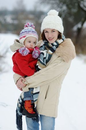Young mother holding her little winter girl in a red coat Stock Photo - 6226337