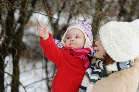Young mother holding her little winter girl in a red coat Stock Photo - 6226393
