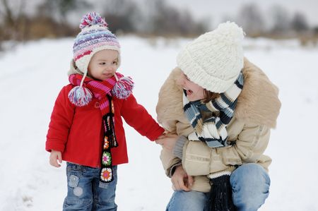 Little winter baby girl and her young mother in a park photo
