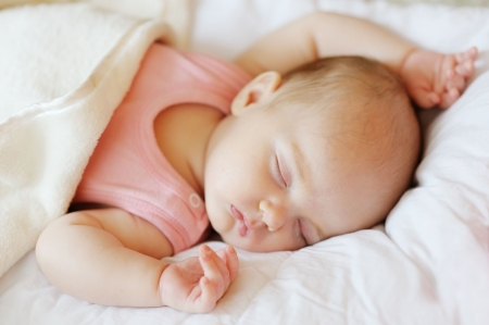 Sweet little newborn baby sleeping in a bed photo
