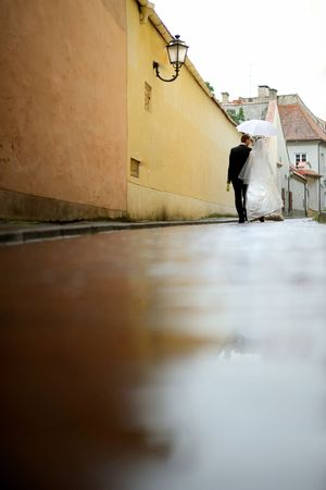 Bride and groom walking under umbrella on a street photo