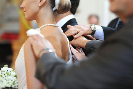 Parents blessing bride and groom during a wedding ceremony photo