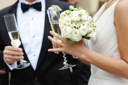 Bride and groom are holding champagne glasses photo