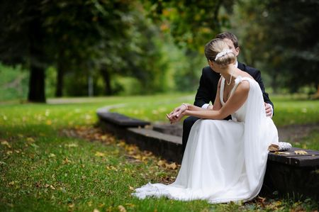 elegancy: Bride and groom sitting in autumn park Stock Photo