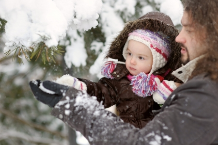 Little winter baby girl and her father touching tree branch photo