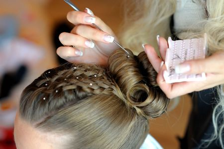Womans stylists hands making a fancy hairstyle