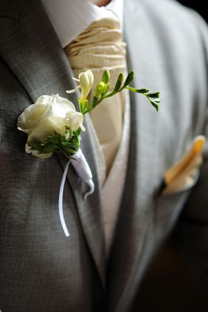 boutonniere: White fressia boutonniere on grooms suit