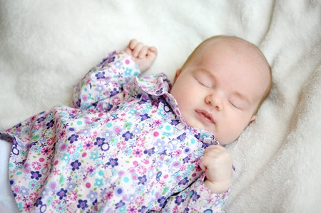 Sweet sleeping baby on a white blanket photo