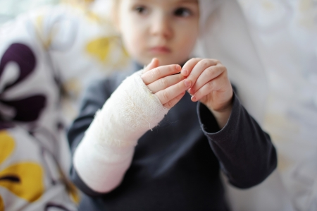Little baby girl showing her bandaged hand Stock Photo