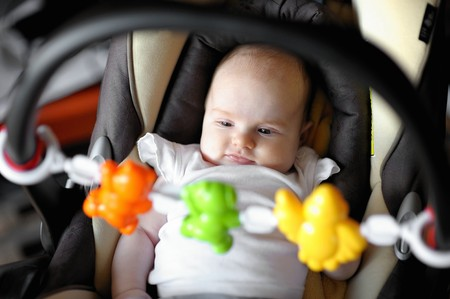 Little two month baby playing in a carseat photo