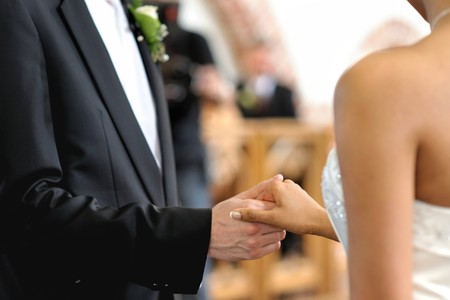 Bride and groom holding each others hands during wedding ceremony Stock Photo