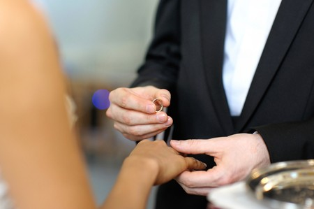 Groom putting a ring on brides finger during wedding ceremony