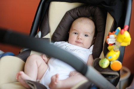 Little two month baby playing in a carseat
