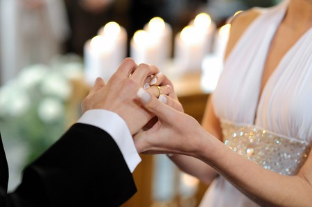 Bride putting a ring on grooms finger during wedding ceremony Stock Photo