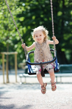 chain swing ride: Swinging preschooler girl having fun Stock Photo
