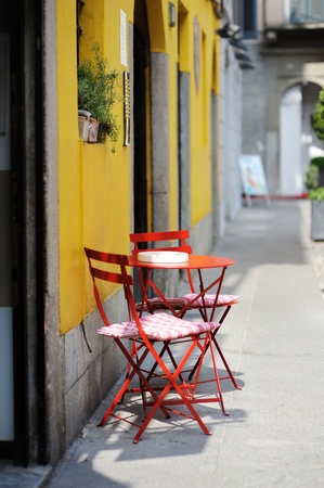 outdoor cafe: Red chairs against a yellow painted wall in Italy Stock Photo