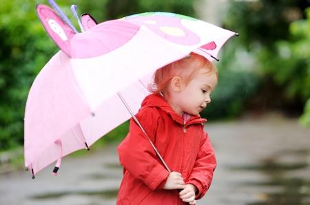 Rozkošná batole dívka na deštivý den na podzim