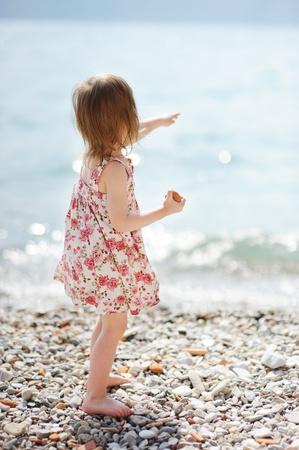 Little girl having fun on a pebble beach
