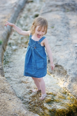 Cute little girl playing  in a creek photo