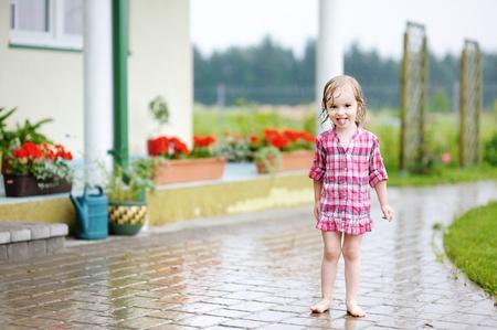 Little girl having fun under the rain in summer