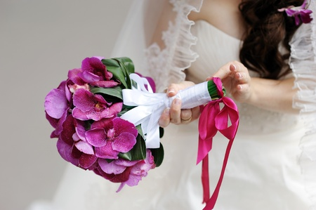 Bride holding beautiful purple bridal bouquet photo