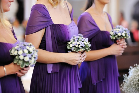 purple dress: Row of bridesmaids with bouquets