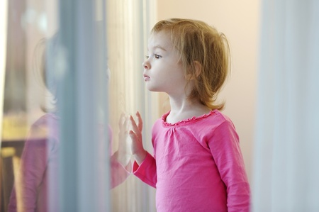 Curious little girl looking out of the window photo