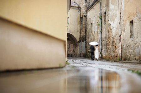 people from behind: Bride and groom walking away under an umbrella Stock Photo