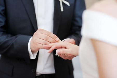 Groom putting a wedding ring on bride