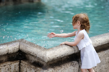 Funny little girl having fun by a city fountain photo
