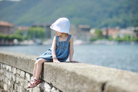 parapet: Little girl sitting on a stone parapet
