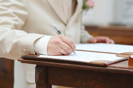 Groom signing marriage license or wedding contract photo